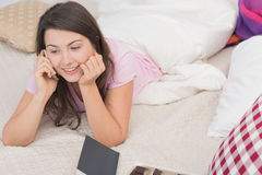 Happy single woman in bed. Talking on cellphone stock photos