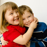 Happy sister and brother hugging each other. Close up of a three-year-old sister and six-year-old brother hugging each other isolated on a white background Royalty Free Stock Photo