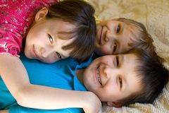 Happy sister with brothers. Two brothers and their sister hugging on a bed at home royalty free stock images