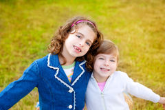 Happy sister girls in winter park grass playing Royalty Free Stock Images