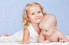 Happy sister hugging baby brother royalty free stock photography