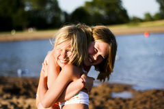 Happy sisters. Two girls hugging with happy smiles on faces while at the beach royalty free stock photography