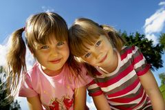 Happy sisters. Two cute little girls smiling in the summer park Royalty Free Stock Photo