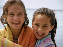 Happy sisters. Portrait of a two young sisters (best friends) after leaving the Adriatic  sea wrapped in a towel spending, laughing and having fun at  holidays Royalty Free Stock Images