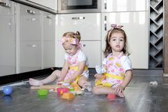 Happy sisters children girls bake cookies, knead dough, play with flour and laugh in the kitchen Royalty Free Stock Photos
