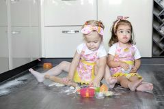 Happy sisters children girls bake cookies, knead dough, play with flour and laugh in the kitchen Stock Photo