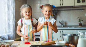 Happy sisters children girls bake cookies, knead dough, play wit. H flour and laugh in the kitchen Royalty Free Stock Photo