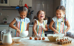 Happy sisters children girls bake cookies, knead dough, play wit royalty free stock photos