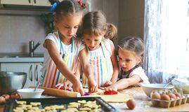 Happy sisters children girls bake cookies, knead dough, play wit. H flour and laugh in the kitchen Stock Photos