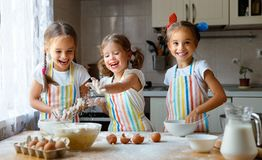Happy sisters children girls bake cookies, knead dough, play wit. H flour and laugh in the kitchen stock photography