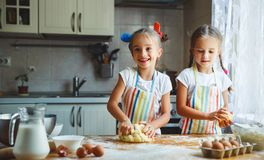 Happy sisters children girls bake cookies, knead dough, play wit. H flour and laugh in the kitchen Royalty Free Stock Photos