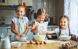 Happy sisters children girls bake cookies, knead dough, play wit. H flour and laugh in the kitchen Stock Photo