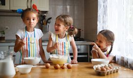 Happy sisters children girls bake cookies, knead dough, play wit. H flour and laugh in the kitchen royalty free stock photography