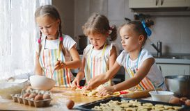 Happy sisters children girls bake cookies, knead dough, play wit. H flour and laugh in the kitchen stock image