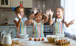 Happy sisters children girls bake cookies, knead dough, play wit Royalty Free Stock Image