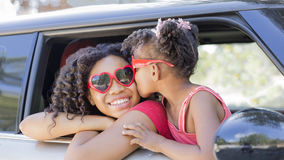 Happy sisters or friends on a Summer Joy Ride. Summer fun! Happy girls or sisters with heart shaped sunglasses in car window. Younger girl kisses older girl on Stock Photography