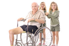 Happy sisters with grandpa. Happy sisters pushing eldery man in wheelchair isolated on a white background Royalty Free Stock Photography