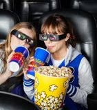 Happy Sisters Having Snacks In 3D Movie Theater Royalty Free Stock Photography