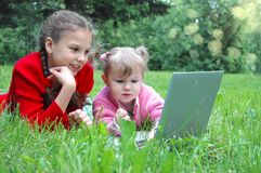Happy sisters with laptop on the meadow Stock Image