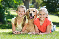 Happy sisters lying with their dog in the park Stock Photo