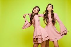 Happy sisters in pink dresses smiling and standing together. Brunette twins with long hair in pink dresses posing at camera on yellow studio background. Happy stock photos