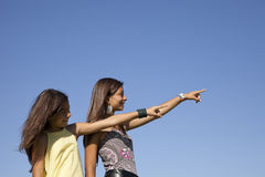 Happy sisters pointing away stock photo