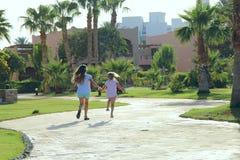 Happy sisters run on footpath in tropical resort stock image