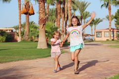 Happy sisters run on footpath in tropical resort. Sisters relaxing on vacations royalty free stock photo