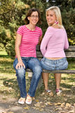 Happy sisters sitting on a bench Stock Photo