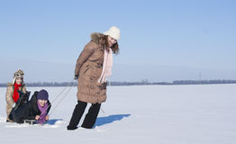 Happy sisters sledding. At winter time Royalty Free Stock Photography
