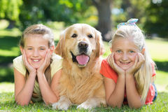 Happy sisters smiling at camera with their dog Stock Photo