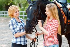 Happy sisters  standing with the horse Stock Images