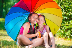 Happy sisters under colorful umbrella in park Royalty Free Stock Photo