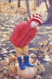 Happy boy sitting on pumpkin outdoors in autumn. Helloween. royalty free stock photo