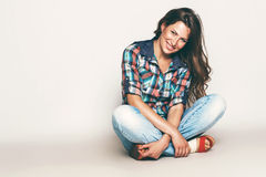 Happy sitting woman in check shirt. In studio Stock Images