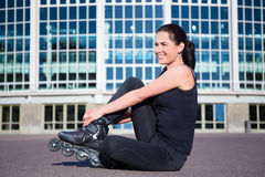 Happy sitting woman on inline skates Stock Photography