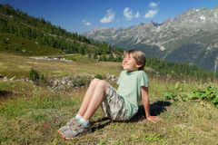 A happy six years boy blinks in sunlights. On mountain slope Royalty Free Stock Photography