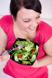 Happy size plus woman eating a salad Royalty Free Stock Photography