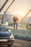 Happy skateboarder on the bridge playing guitar on his skate boa Stock Photography