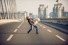 Happy skateboarder on the bridge playing guitar on his skate boa Royalty Free Stock Images