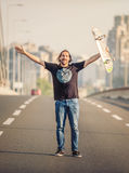 Happy skateboarder standing on the road bridge and raising his h Stock Photography