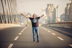 Happy skateboarder standing on the road bridge and raising his h Royalty Free Stock Photo