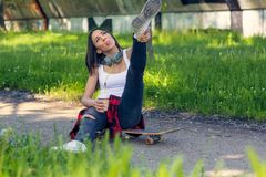 Happy skateboarder woman sitting on skateboard and drink coffee royalty free stock photos