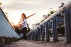 Happy skater girl walking through city holding longboard in the sunset. Youth culture freedom concept stock photos