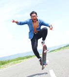 Happy skater playing skateboard with flipping trick Royalty Free Stock Photography