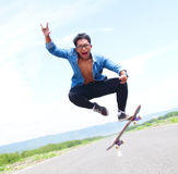 Happy skater playing skateboard with flipping trick Royalty Free Stock Photos