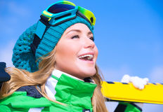Happy skier girl. Closeup portrait of cute happy skier girl on blue sky background, extreme winter sport, active lifestyle concept royalty free stock image