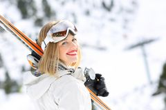 Happy skier girl ready to ski in a slope. Portrait of a happy skier girl ready to ski in a snowy slope stock image