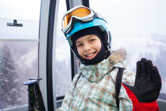 Happy skier girl on ski lift. Royalty Free Stock Photo