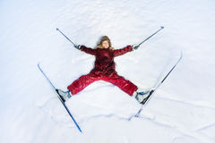 Happy skier laying as a star on the snow Royalty Free Stock Photo